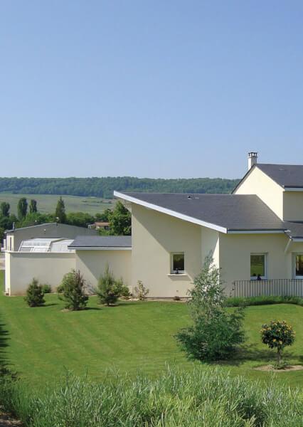 Maison en pierre de couleur blanche à 2 niveaux avec toits de couleur noir, jardin et garage au sous