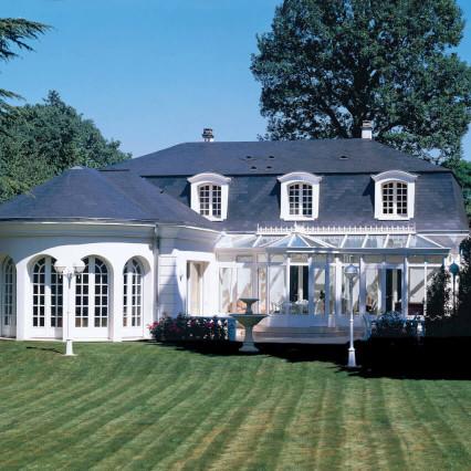 Maison vintage en pierre blanche avec toi bleu sombre, avec veranda et jardin