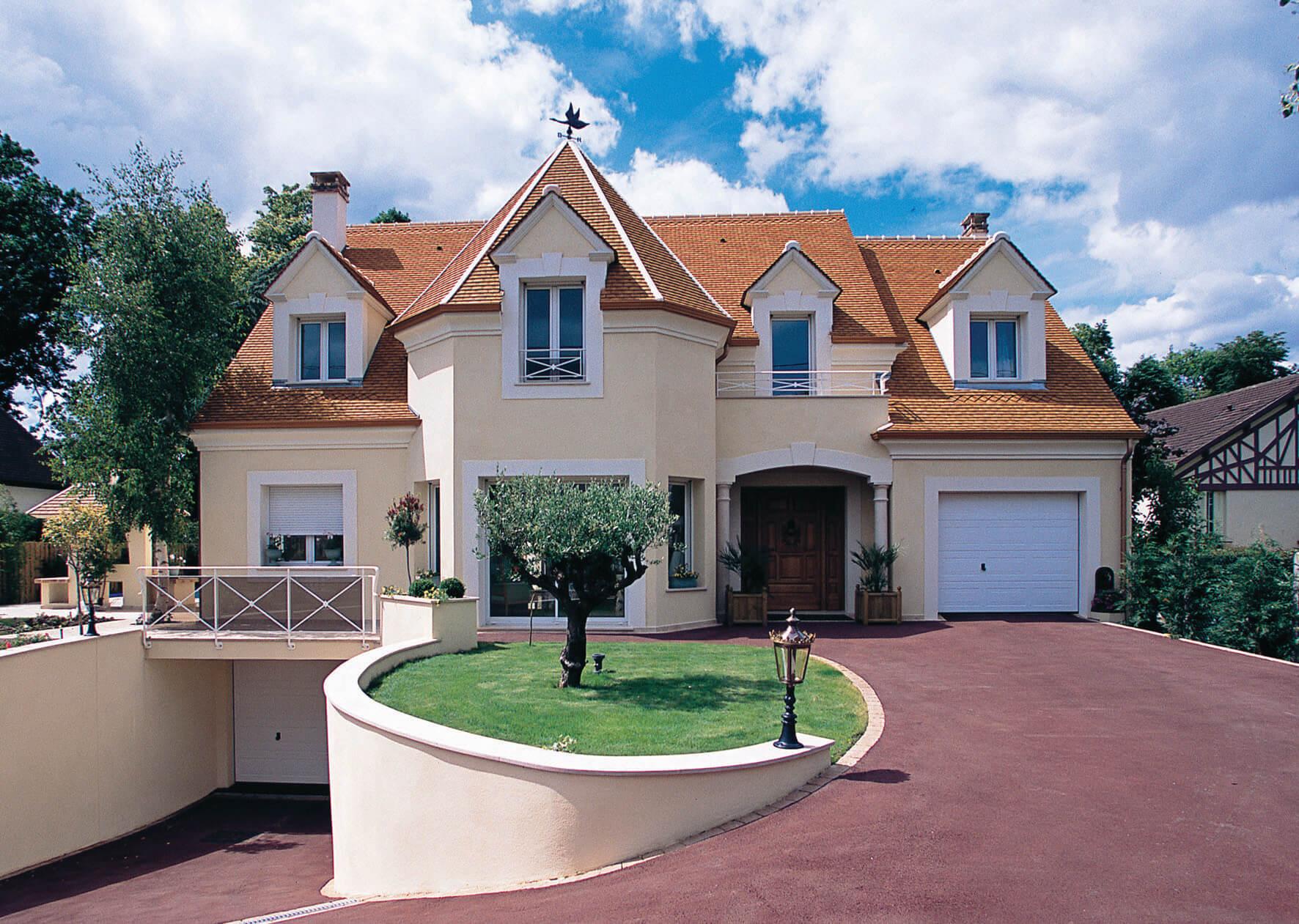 Maison en pierre de couleur belge à toi orange clair avec garage au sous-sol